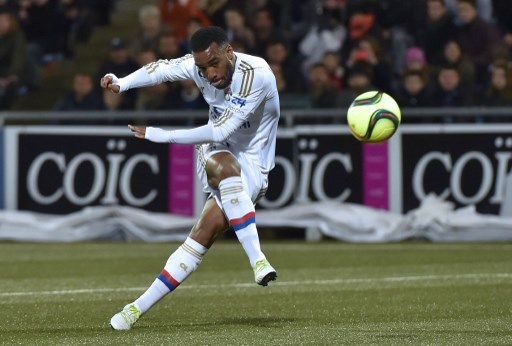 """(FILES) This file photo taken on April 03, 2016 shows Lyon's French forward Alexandre Lacazette kicks the ball to score during the French L1 football match between Lorient and Lyon at the Moustoir stadium in Lorient, western France. Arsenal agreed a deal to sign France striker Alexandre Lacazette from Lyon for a reported club-record 60 million euros ($68m, £52.56m), the Premier League club confirmed on July 5. The transfer fee is also a new record sale for the Ligue 1 outfit, while Arsenal said the 26-year-old had signed a """"long-term contract"""".  / AFP PHOTO / LOIC VENANCE"""