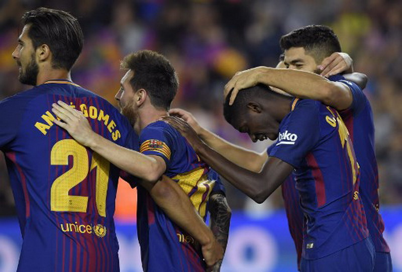 Barcelona's Uruguayan forward Luis Suarez (R) celebrates with Barcelona's French forward Ousmane Dembele (2R), Barcelona's Argentinian forward Lionel Messi (C) and Barcelona's Portuguese midfielder Andre Gomes (L) after scoring during the Spanish Liga football match Barcelona vs Espanyol at the Camp Nou stadium in Barcelona on September 9, 2017. / AFP PHOTO / LLUIS GENE