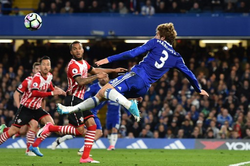 Chelsea's Spanish defender Marcos Alonso (R) fails to score with this acrobatic attempt during the English Premier League football match between Chelsea and Southampton at Stamford Bridge in London on April 25, 2017. Chelsea won the game 4-2. / AFP PHOTO / Glyn KIRK / RESTRICTED TO EDITORIAL USE. No use with unauthorized audio, video, data, fixture lists, club/league logos or 'live' services. Online in-match use limited to 75 images, no video emulation. No use in betting, games or single club/league/player publications.  /